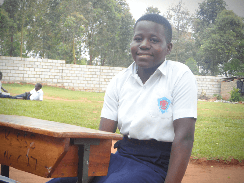 Health and Rights: Catherine wears her school uniform and sits at a desk outside of her school in Uganda. Behind her is a green field and beyond that a white brick wall and trees.