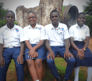 Health and Rights: Four students, 2 boys and 2 girls including Catherine, sit outside of their school in Uganda.