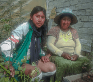 Jhoselin at left crouches next to her mother in the urban garden in Bolivia. They are surrounded by a brick wall and plants grow around them.