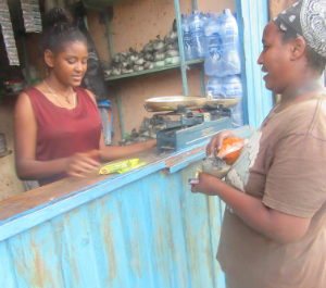 A teenage girl behind a stall selling products to a woman