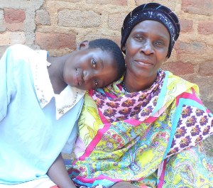 A young girl rests her head on the shoulder of her grandmother, both lovingly looking into the camera