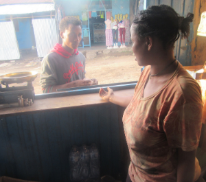 a woman behind a stall sells products to a young man