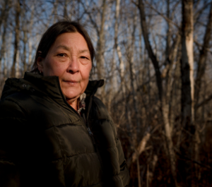 an elder stands in a forest, looking into the camera