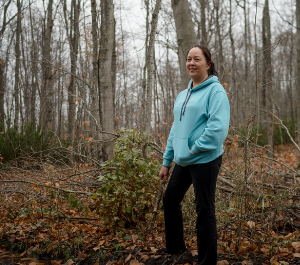 a woman stands in a forest, smiling for the camera