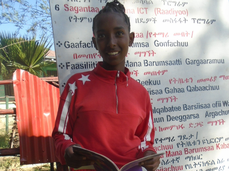 a teenage girl stands in front of a sign written in amharic and holding an open book