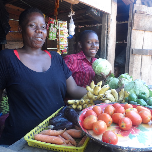 Women and her daughter stand in front of their vegetable produce