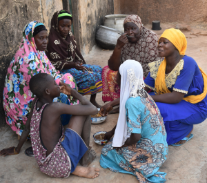 a family sits on the ground sharing a meal