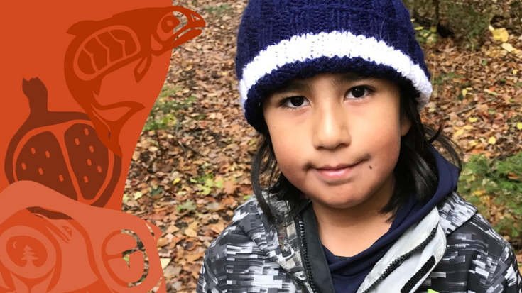 a little boy in a toque stands in a forest