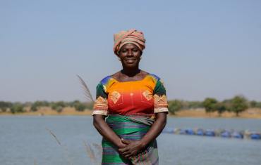 a woman stands in front of a lake