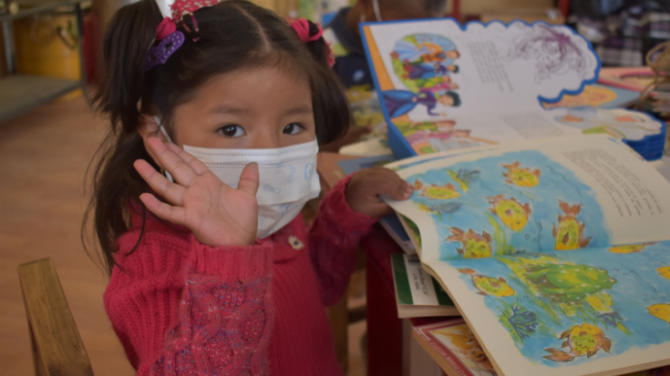 a little girl in a mask reads a book and waves to the camera