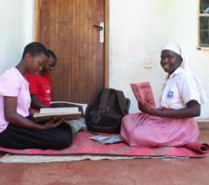 three young girls sit holding workbooks, doing homework