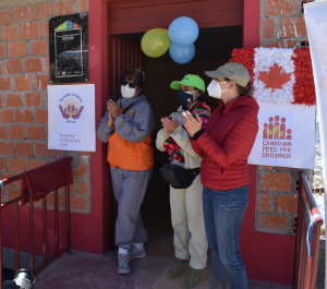 three women in masks stand in front of a community centre