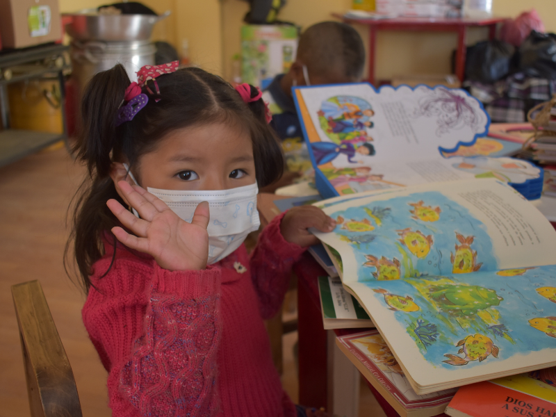 little girl in mask waves while reading a book
