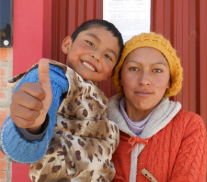 a woman holds a child in her arms who is giving the camera a thumbs up