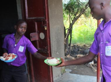 a boy serves another boy a school meal